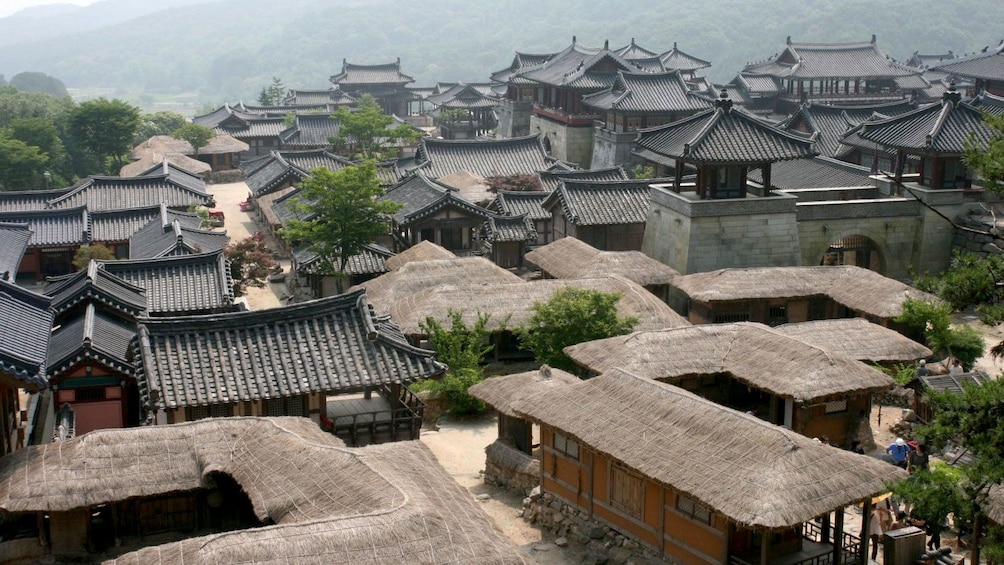 Traditional buildings at a Korean Folk Village nestled beside forested hills hand mountains