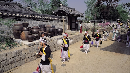 Musicians in traditional costumes walking through Namsangol Hanok Village