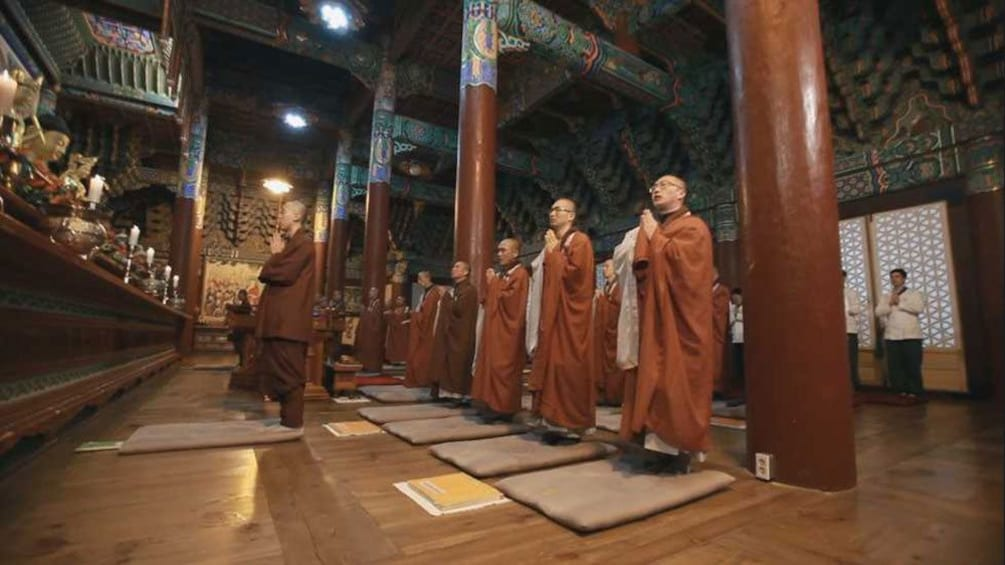 Show item 2 of 5. Monlk praying in a Buddhist temple in Seoul