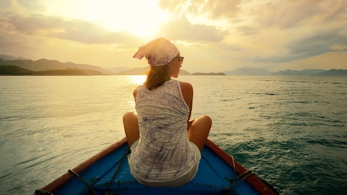 Woman sitting on the bow of a fishing boat at sunset in Pulau Ketam