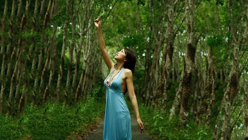 Woman in a blue dress holding a leaf and surrounded by trees in Sekinchan
