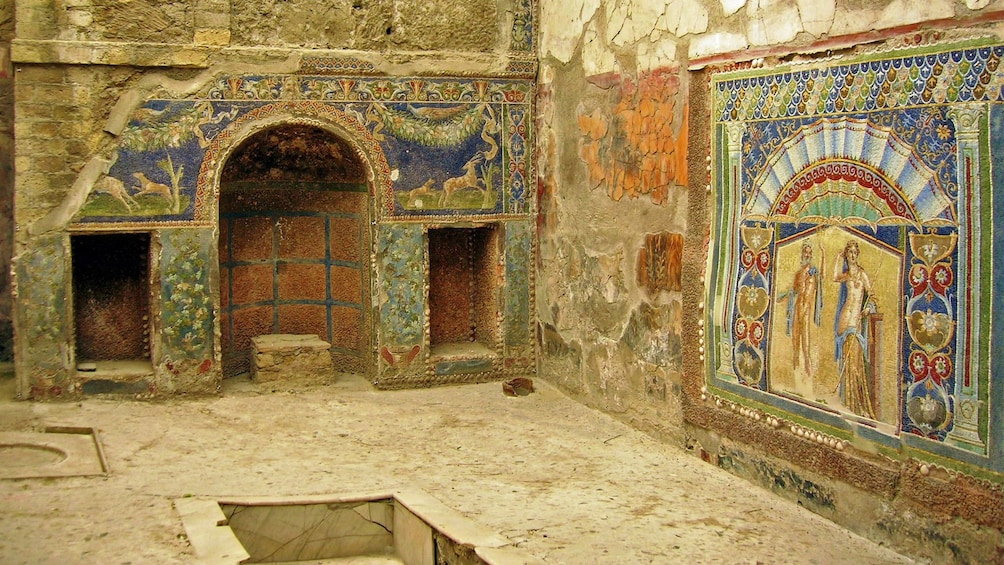 Interior of ancient building with artwork on the walls in Pompeii