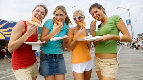 Four women eating pizza on a boardwalk in San Diego