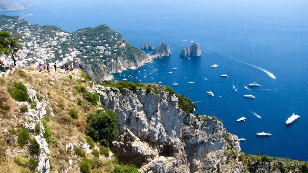 People on a grassy cliff looking down at the Amalfi Coast