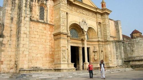 Pair of women walking outside the Catedral Primada de América in Santo Domingo