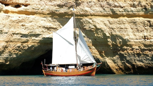 Sailboat passing a sea cave in Algarve