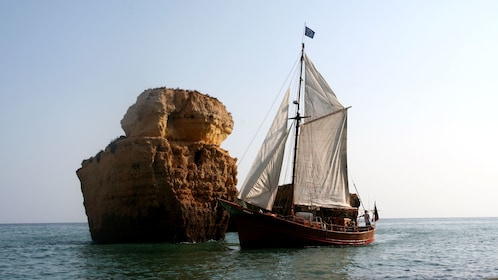 Pirate-themed sailboat alongside a rock formation jutting out of the water off the coast of Algarve