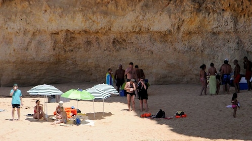 Beachgoers relaxing on the sand on the coast of Algarve
