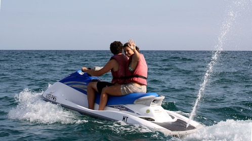 Jet skiing couple in the water off the coast of Algarve