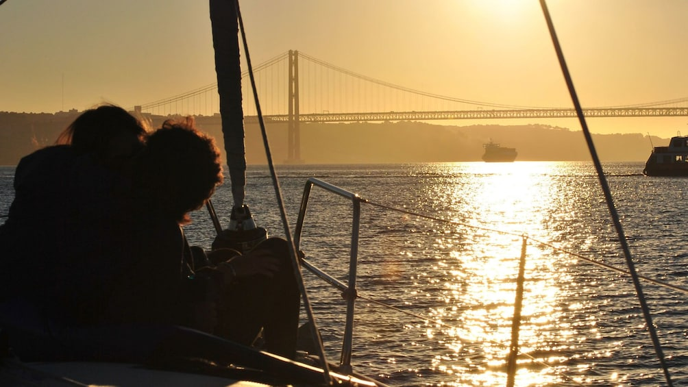 Foto 5 van 7. Couple looking at the sunset from a sailboat in Lisbon