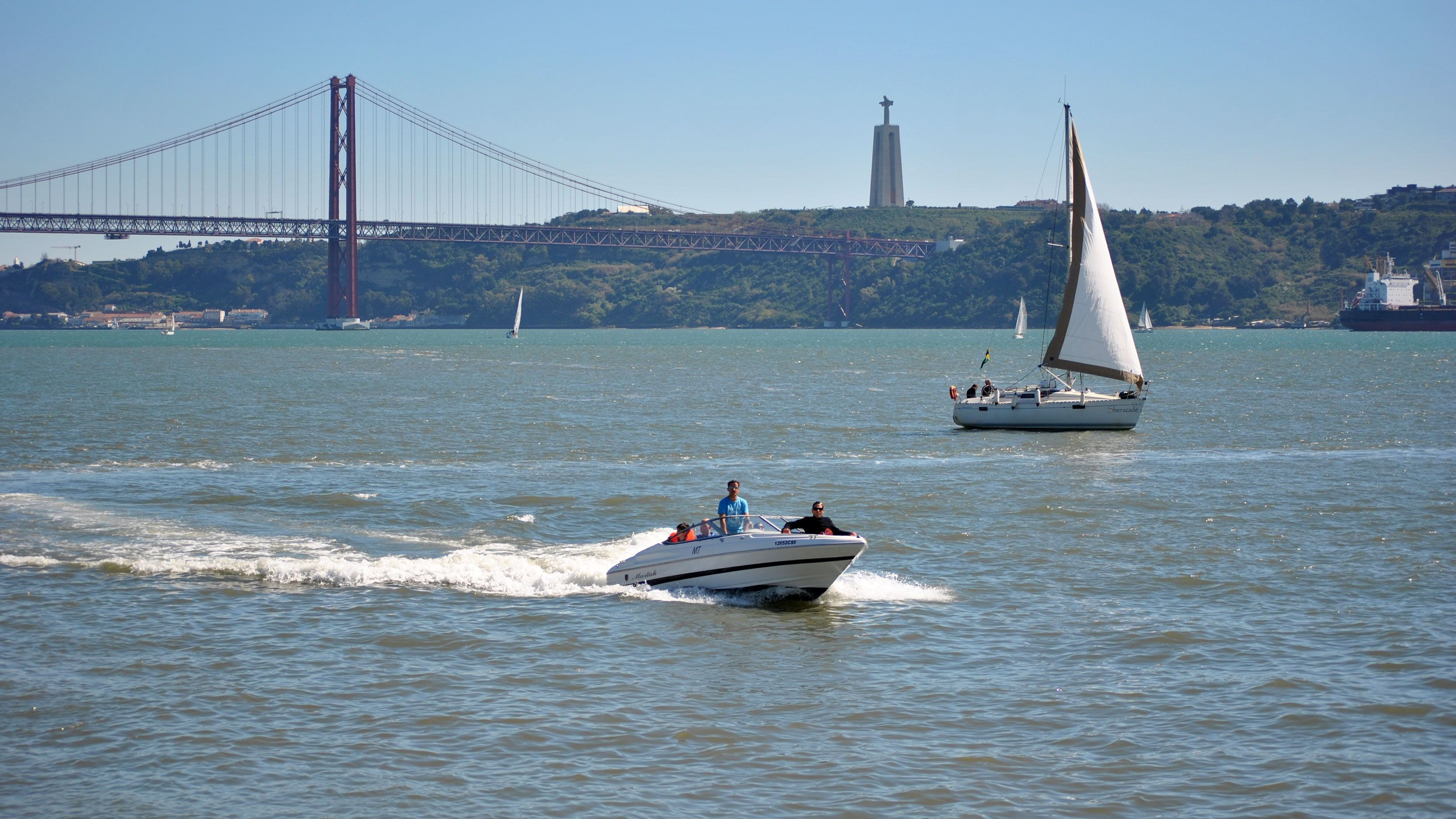 Motor boat on the water with bridge in the background in Lisbon