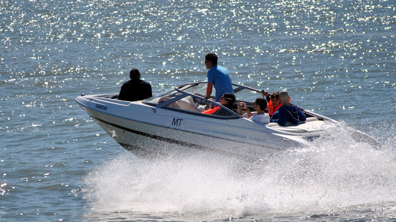 Group speeding through the water on a motor boat in Lisbon