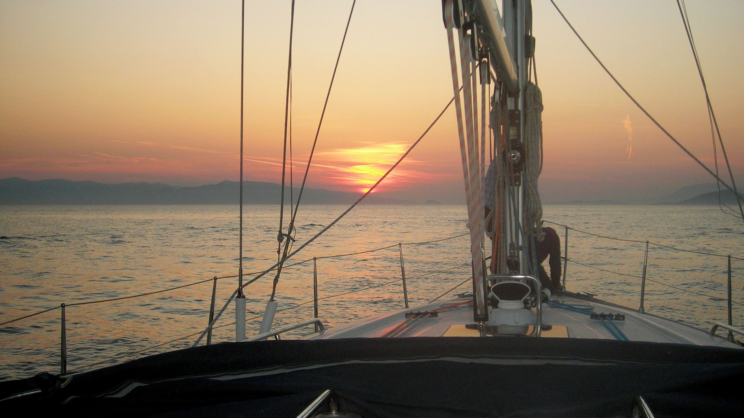 View from the bow of a ship at sunset on the water in Mykonos