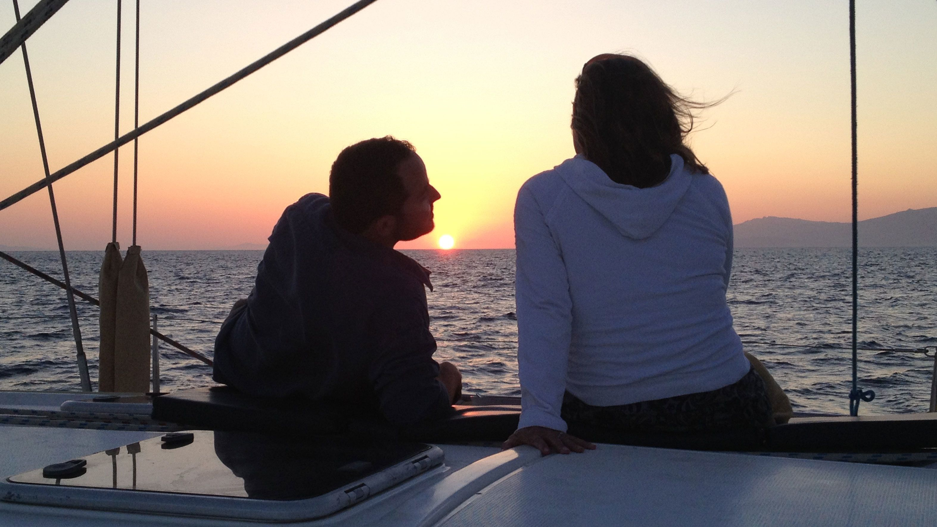 Lounging couple watches the sunset from a boat in Mykonos