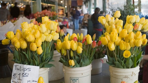 buckets of flowers being sold at the Pike Place Market in Seattle