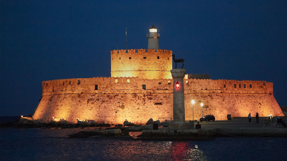 lighthouse and fortress walls lit at night in Rhodes