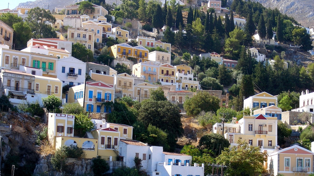 residential homes built into the mountainside in Symi Island