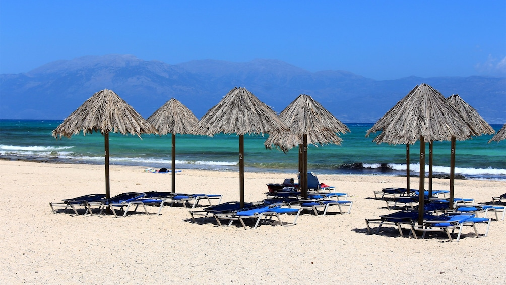 Chaise lounges under umbrellas along the beach shore with mountains in the distance on Crete Island