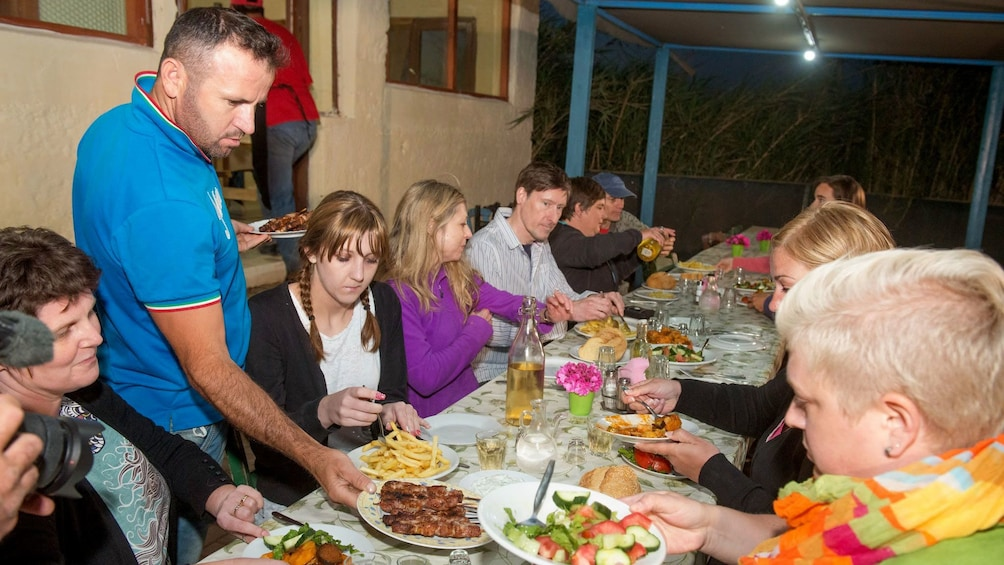 group having dinner under covered outdoor seating area in Crete