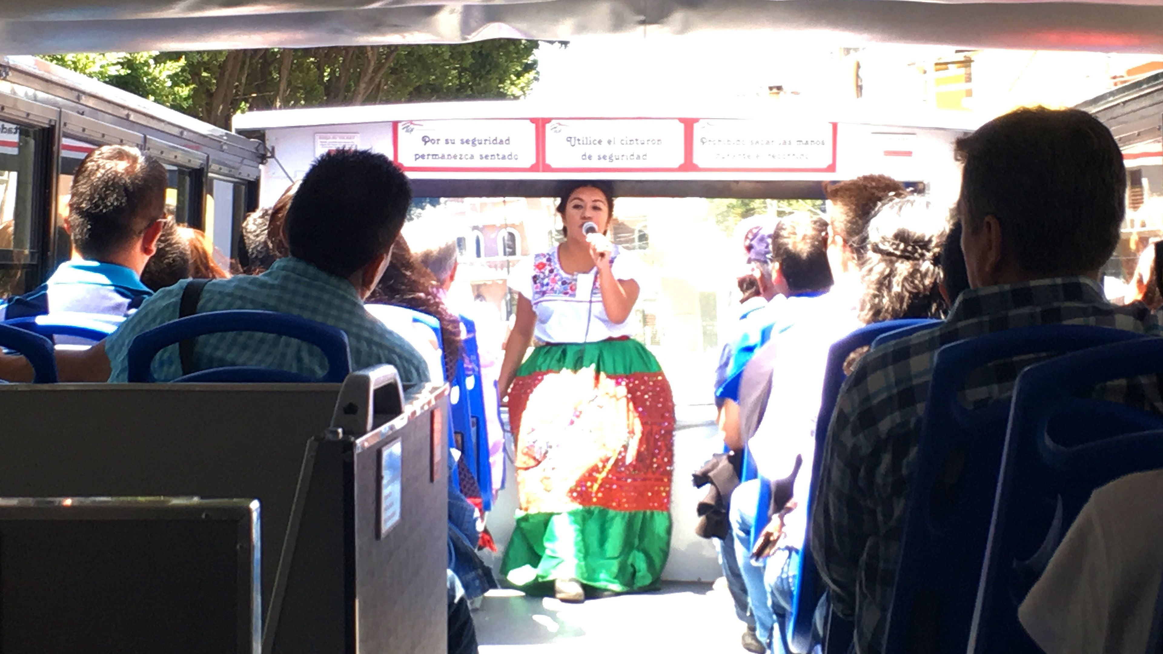 Tour guide talking to tourists on double decker tour bus in Puebla