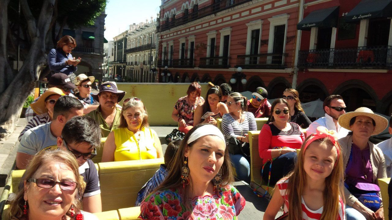 People riding on second level of double decker tour bus in Puebla