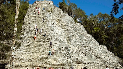 People climbing the stairs of Nohoch Muul Pyramid in Coba