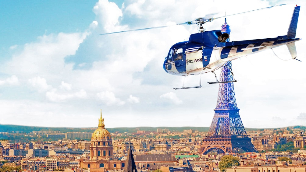 Charger l'élément 1 sur 8. Helicopter flying around the Eiffel Tower in Paris