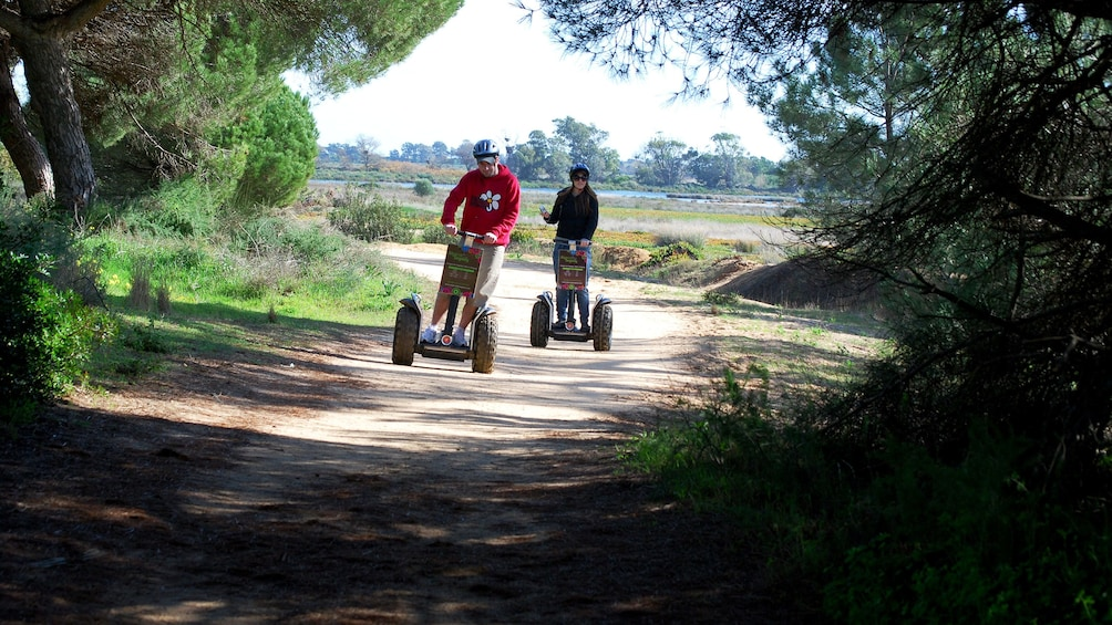 Show item 6 of 6. Two people riding segways down a dirt path at a natural park in Algarve