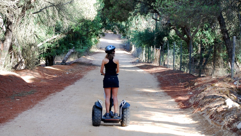 Show item 3 of 6. Woman riding a segway down a tree lined dirt path at a natural park in Algarve