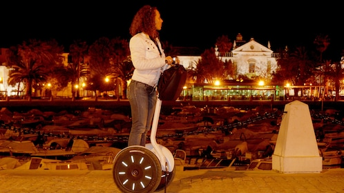 Woman riding a segway past boats in Lisbon at night