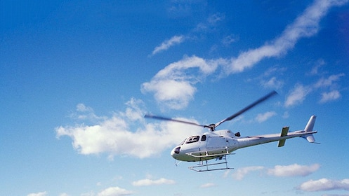 Helicopter flying against a bright blue sky in Los Angeles