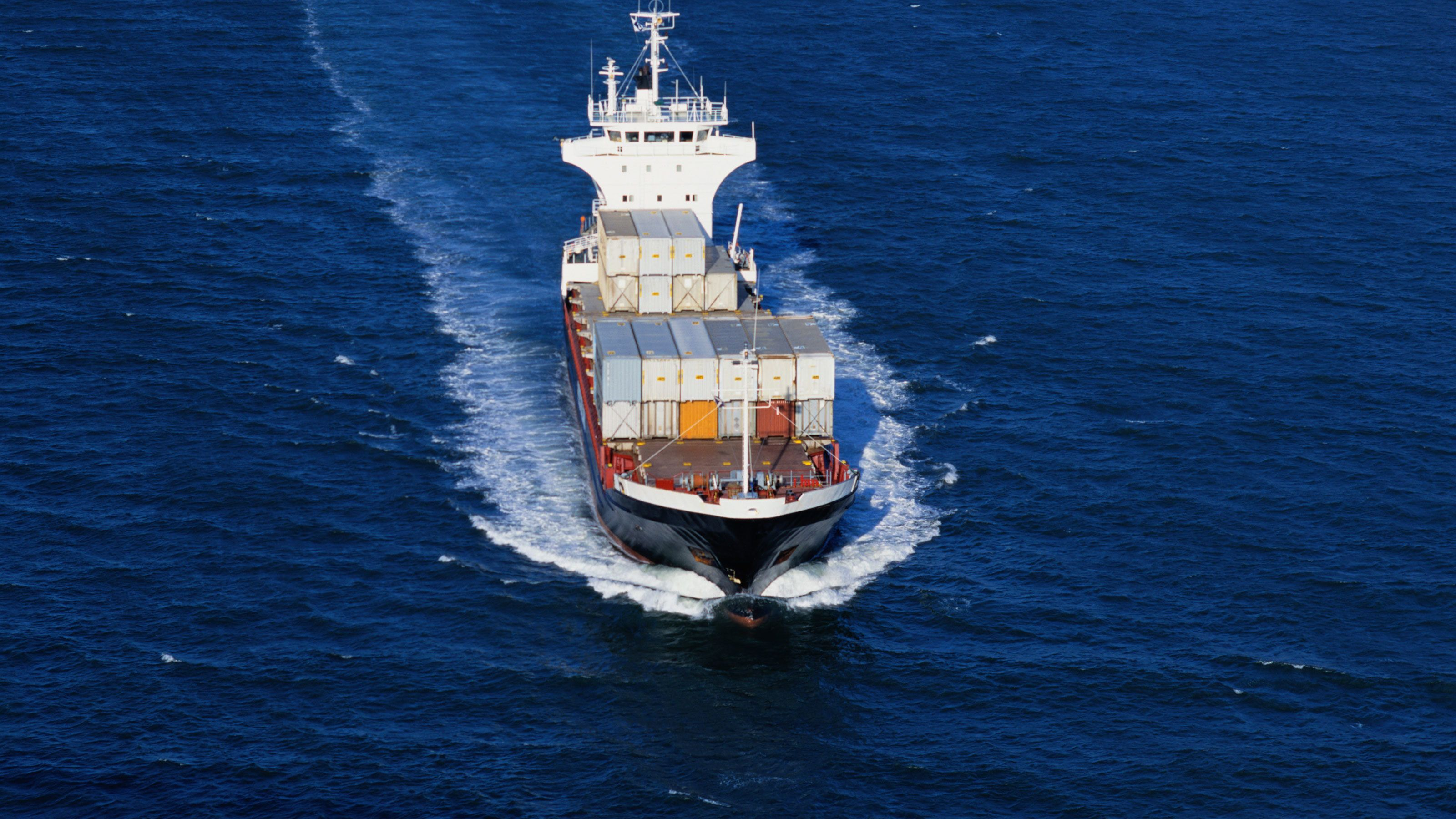 Container ship sailing into a port in Los Angeles with shipping containers
