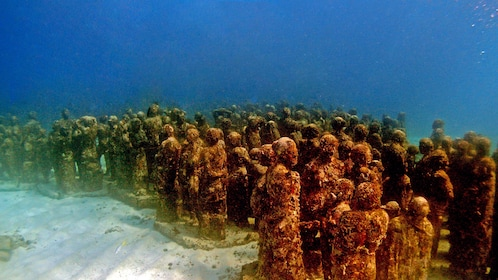 Swimming along underwater statues in Mexico