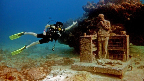 Diver posing with underwater statue in Mexico