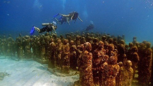 Diving along underwater statues in Mexico