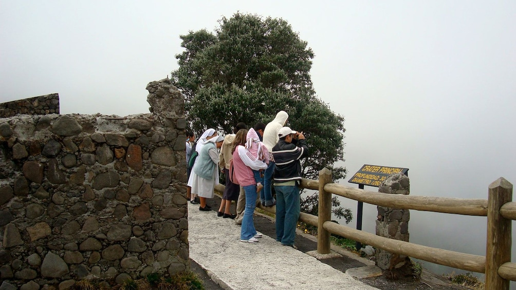 Show item 10 of 10. Tour group peering down into the main crater of the Irazu Volcano