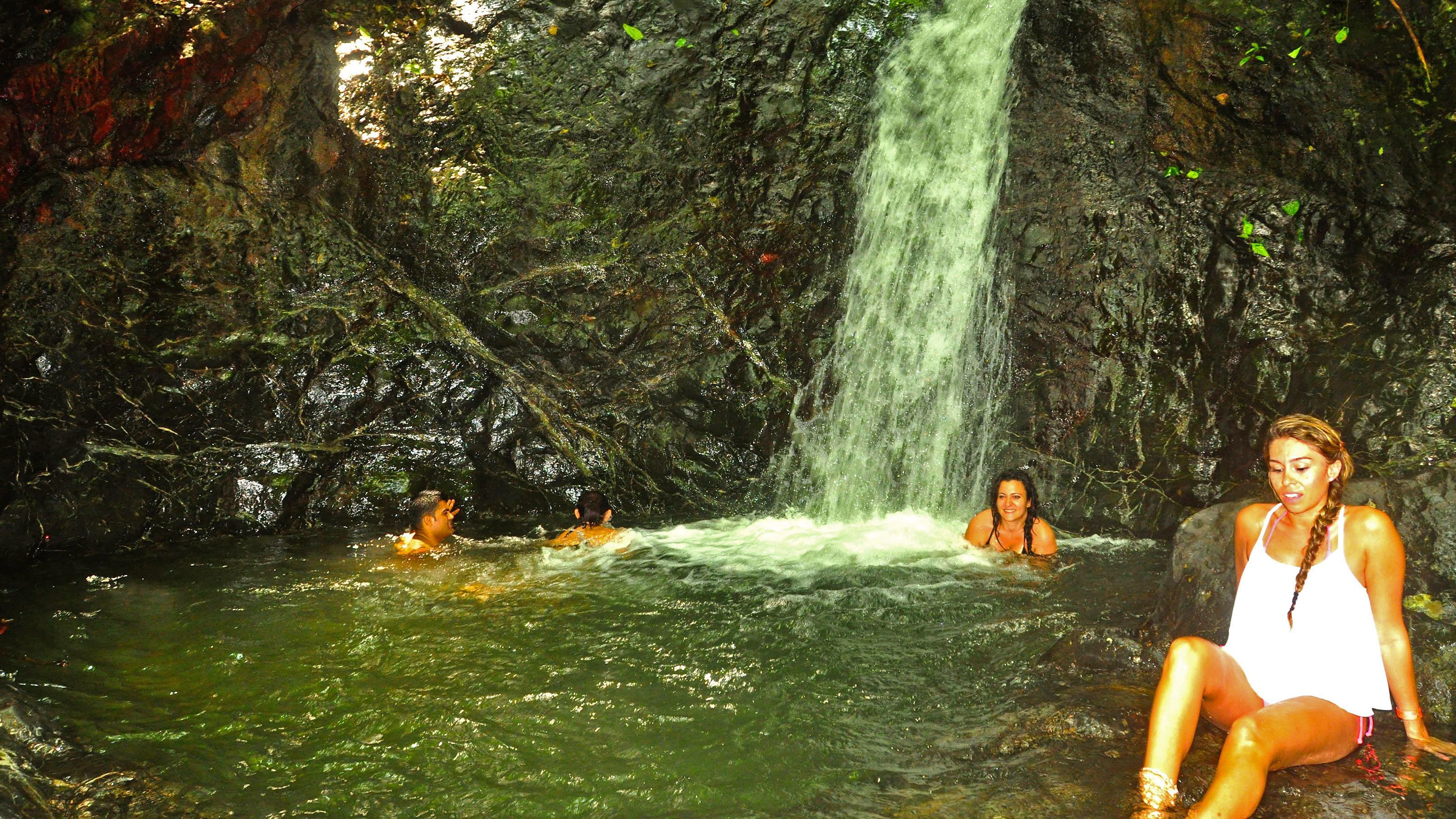Horse riders having a dip in the small waterfall in Jaco