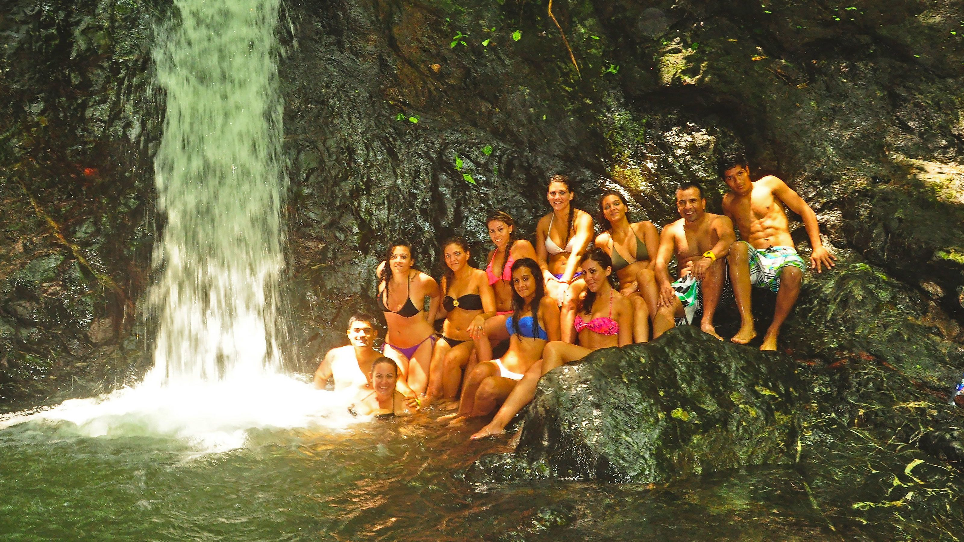 Horse riders huddled at the waterfall in Jaco