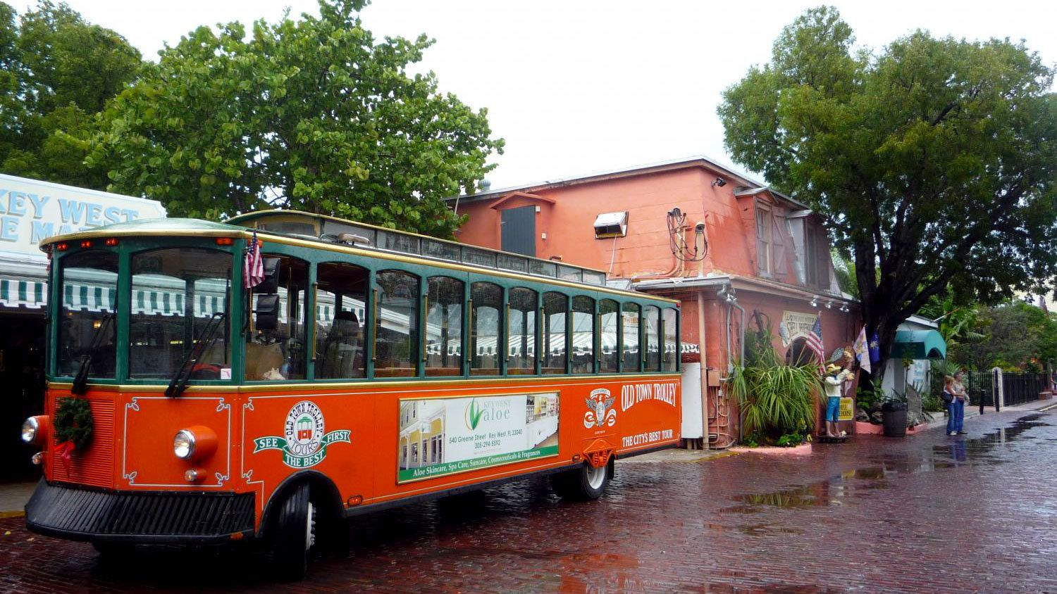 Old town trolley driving past historical buildings in Key West
