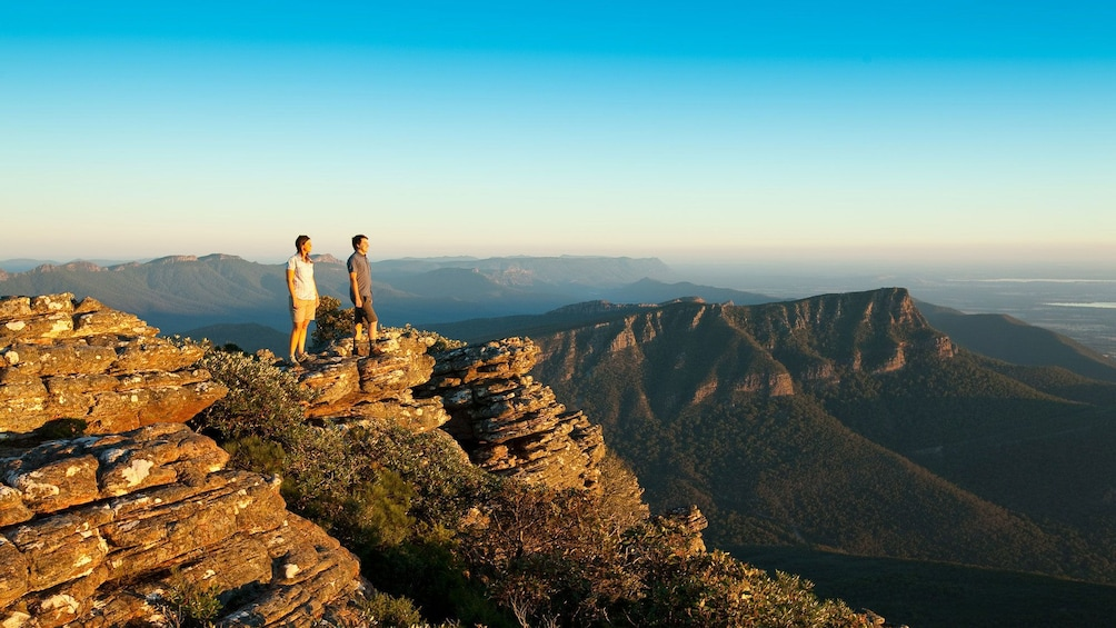 Show item 1 of 10. Two people standing on a rocky peak overlooking Grampians National Park