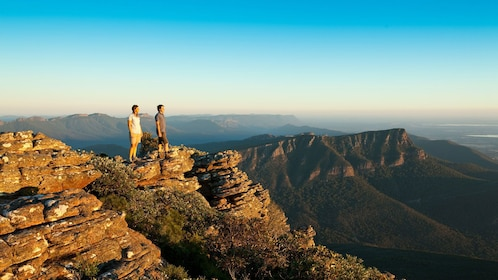 Two people standing on a rocky peak overlooking Grampians National Park