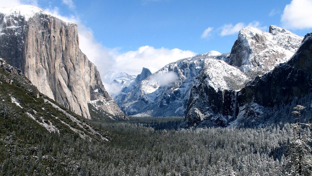 Show item 1 of 10. Snow-covered mountains and forest at Yosemite in California