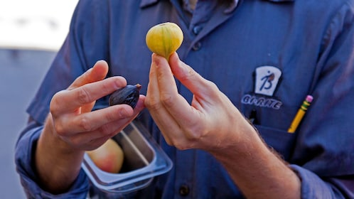 Tour guide holding up figs on food tour in San Francisco