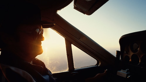 Pilot flying a helicopter at sunset over Los Angeles