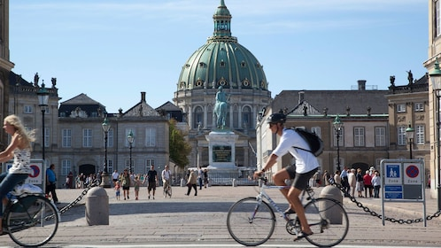 bicyclists riding past Frederik's Church in Copenhangen