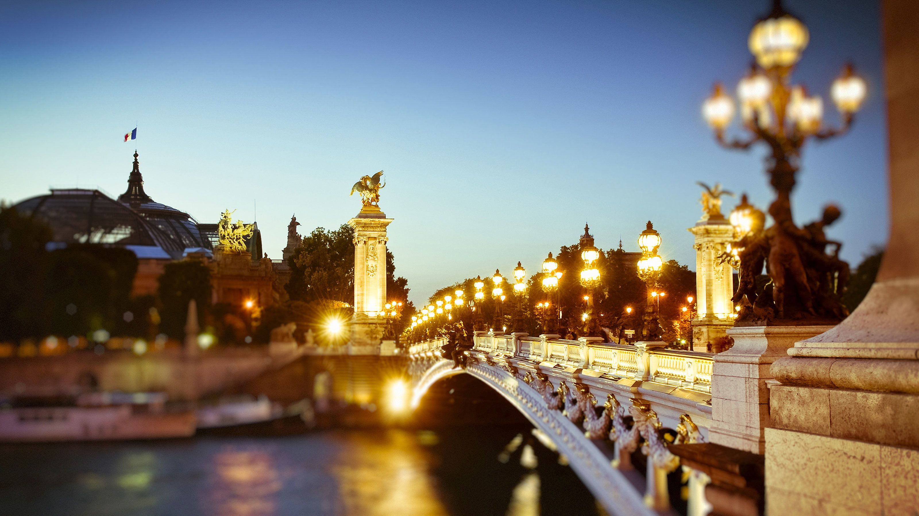 Illuminated bridge across the Seine river in Paris at night