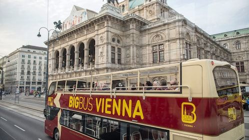 Hop on hop off bus driving past the Vienna State Opera