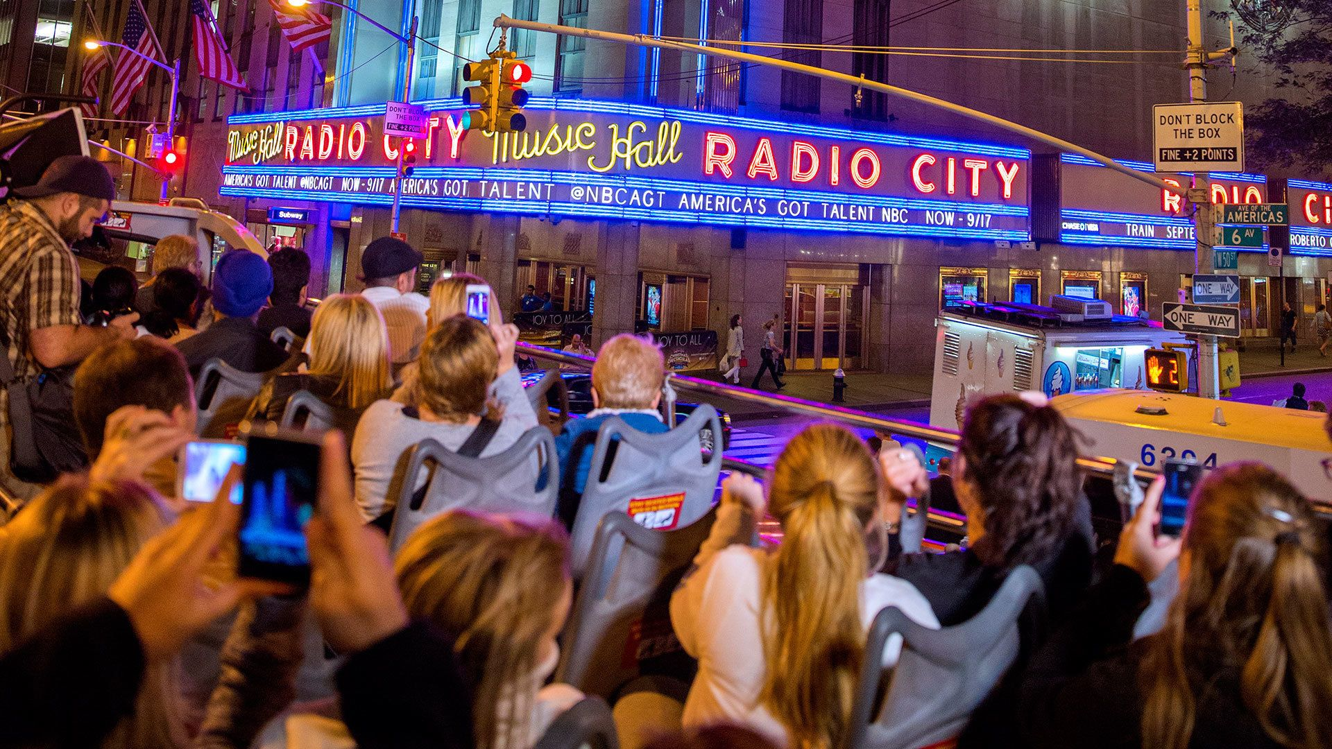 People on the upper level of a tour bus outside Radio City Music Hall in New York