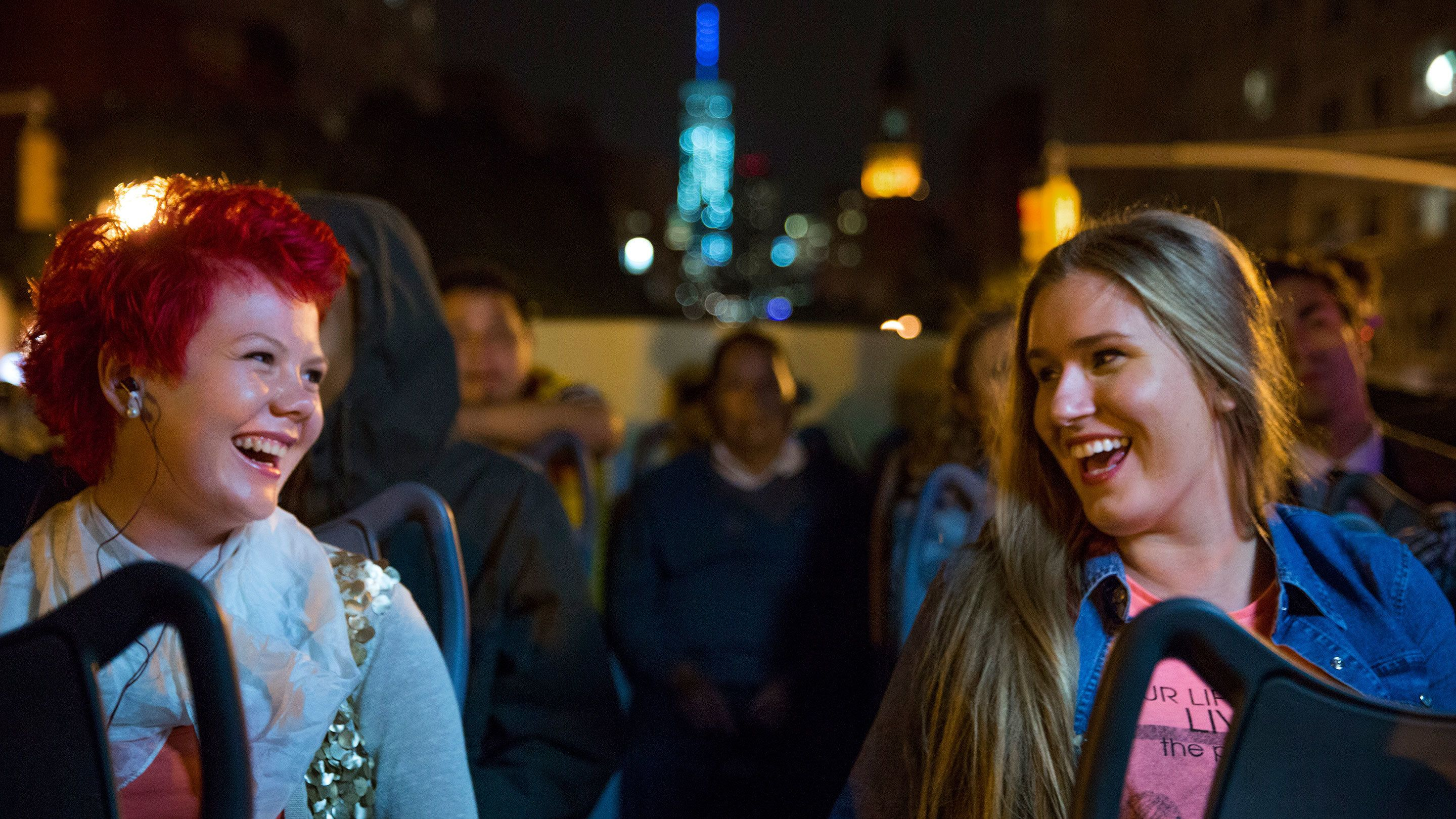 Pair of smiling women enjoying their tour of the city from a double decker bus in New York