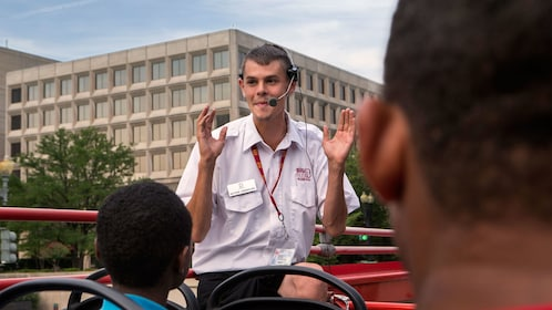 Tour guide describing the sights from the top of a double decker bus in Washington DC